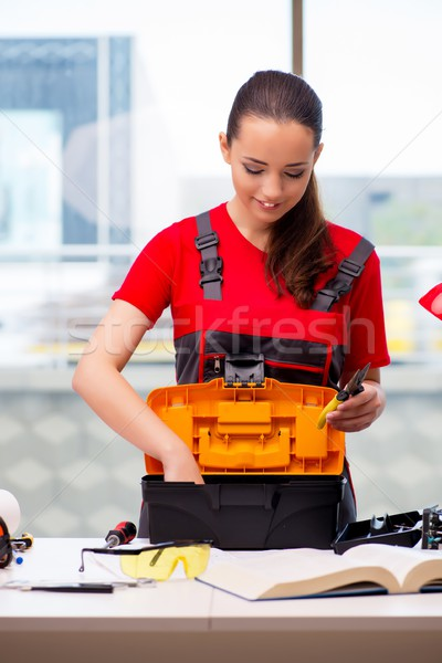The young woman in coveralls doing repairs Stock photo © Elnur