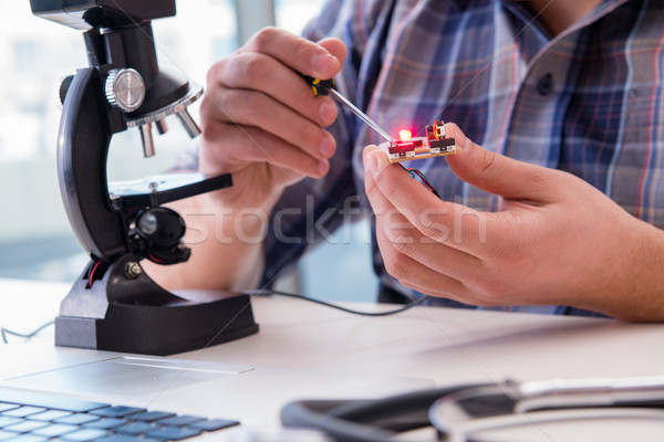 High precision engineering with man working with microscope Stock photo © Elnur