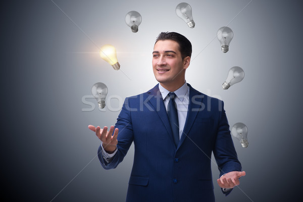 Businessman juggling lightbulbs in new idea concept Stock photo © Elnur
