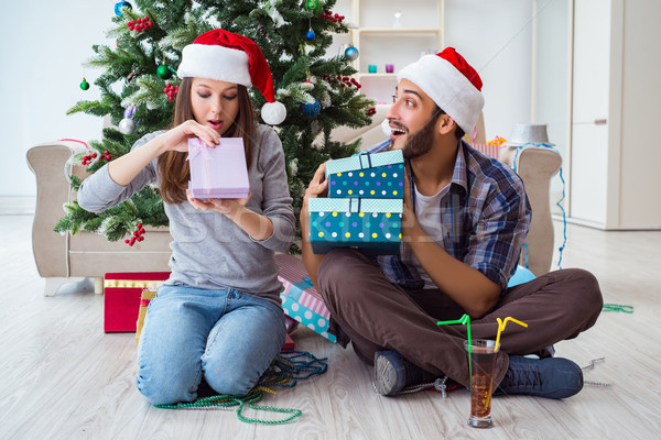 The girlfriend and boyfriend opening christmas gifts Stock photo © Elnur