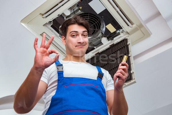 Worker repairing ceiling air conditioning unit Stock photo © Elnur