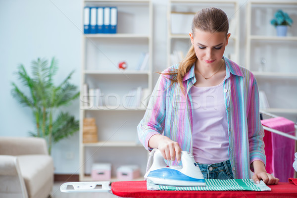 Happy housewife doing ironing at home Stock photo © Elnur