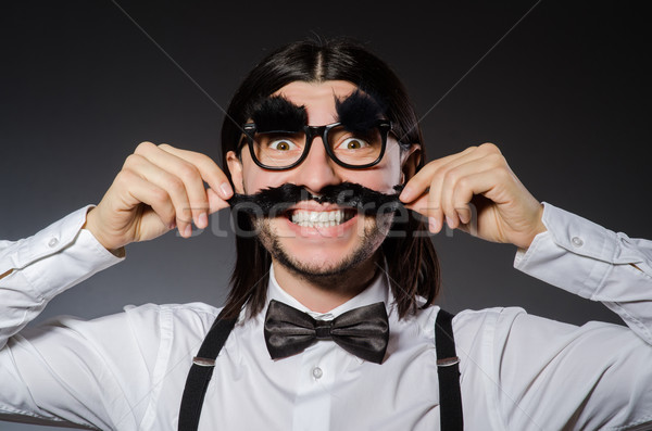 Young man with false mustache and eyebrows isolated on gray Stock photo © Elnur