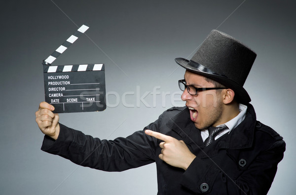 Detective in black coat with clapperboard against gray Stock photo © Elnur