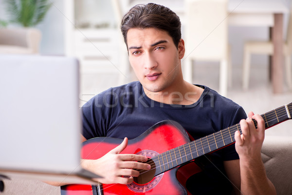 Young man practicing playing guitar at home Stock photo © Elnur