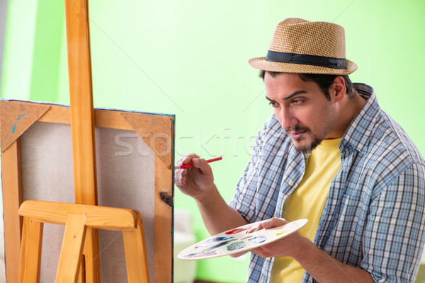 Young male artist working on new painting in his studio Stock photo © Elnur