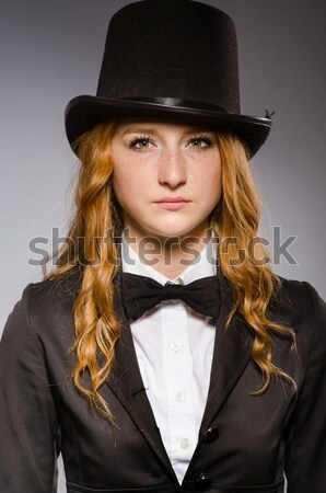Pretty girl wearing retro hat and holding weapon isolated on gra Stock photo © Elnur