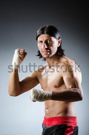 Muscular man with nunchucks on white Stock photo © Elnur