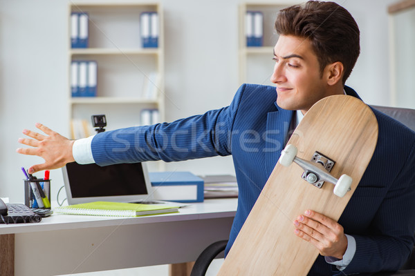 Young businessman with skate in office in sports concept Stock photo © Elnur