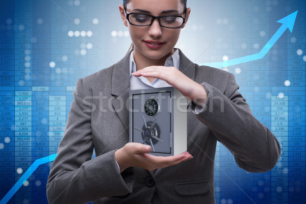 Businesswoman holding metal safe in security concept Stock photo © Elnur
