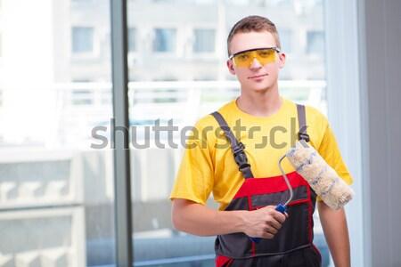 Jeunes travailleur de la construction jaune affaires papier bâtiment Photo stock © Elnur