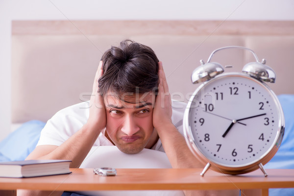 Man in bed frustrated suffering from insomnia with an alarm cloc Stock photo © Elnur