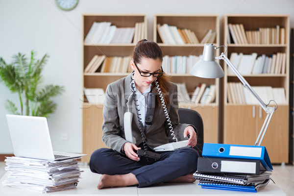 Busy angry businesswoman sitting on the desk in office Stock photo © Elnur