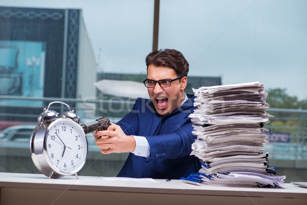 Businessman with pile stack of paper paperwork and an alarm cloc Stock photo © Elnur