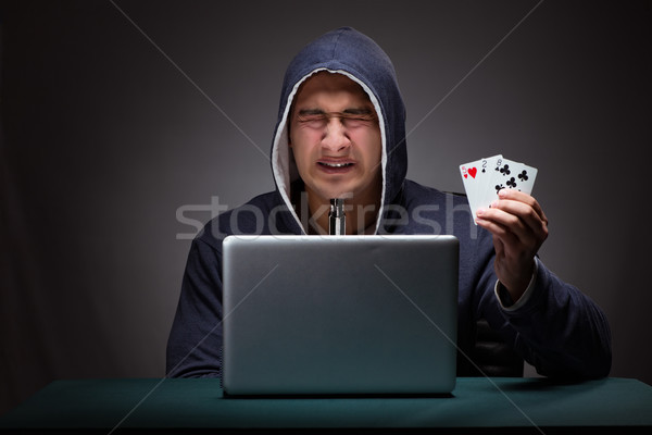 Young man wearing a hoodie sitting in front of a laptop computer Stock photo © Elnur