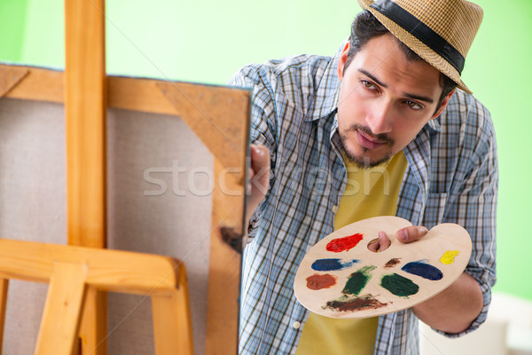 Fiatal férfi művész dolgozik új festmény Stock fotó © Elnur
