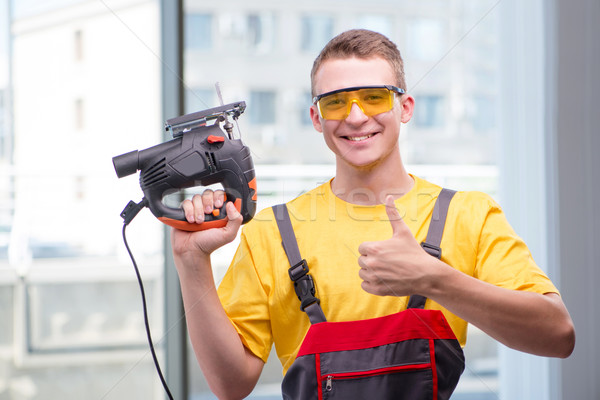 Young construction worker in yellow coveralls Stock photo © Elnur