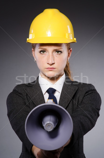 Female engineer with helmet and loudspeaker isolated on gray Stock photo © Elnur