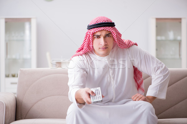 Stock photo: Young arab man watching tv sitting on the sofa