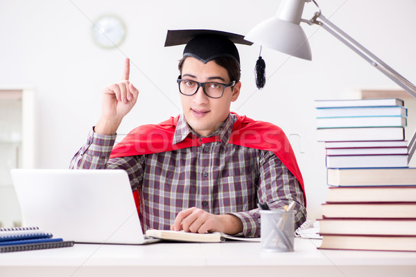 Super hero student wearing a mortarboard studying for exams Stock photo © Elnur