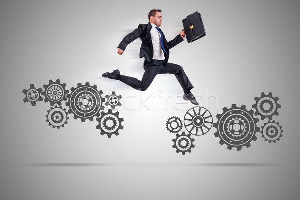 The businessman with cogwheels gear in teamwork concept Stock photo © Elnur