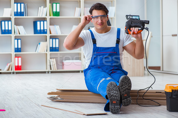 The young worker working on floor laminate tiles Stock photo © Elnur