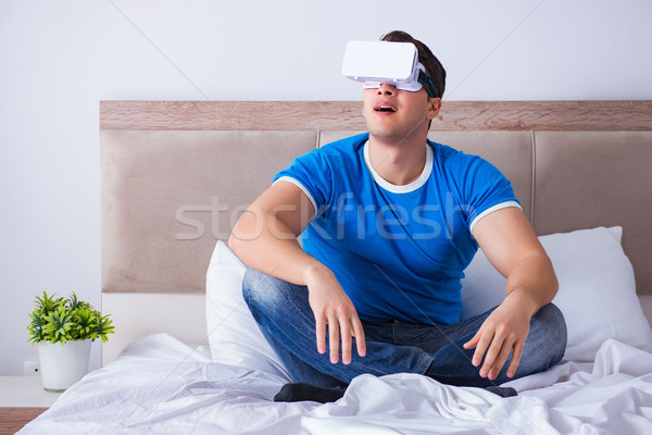 Young man in bed wearing a vr virtual reality head set Stock photo © Elnur