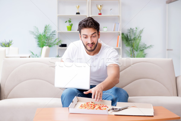 Man eating pizza having a takeaway at home relaxing resting Stock photo © Elnur