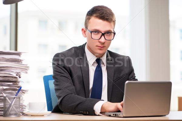 Businessman working with much paperwork Stock photo © Elnur