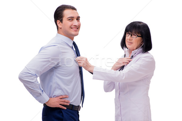 The experienced doctor examining young man isolated on white Stock photo © Elnur