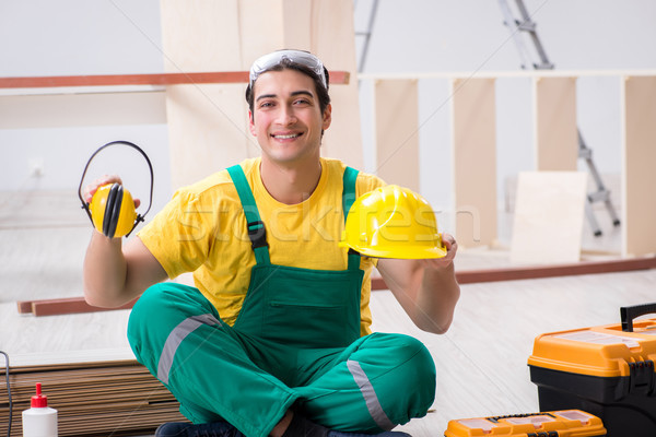 Stock photo: The carpenter wearing yellow hardhat in contractor workshop