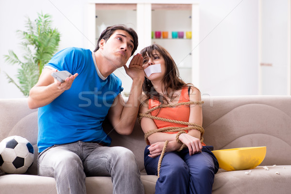 Man tying up his wife to watch sports football Stock photo © Elnur