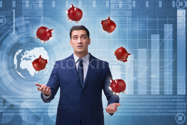 Businessman juggling with piggybanks in business concept Stock photo © Elnur
