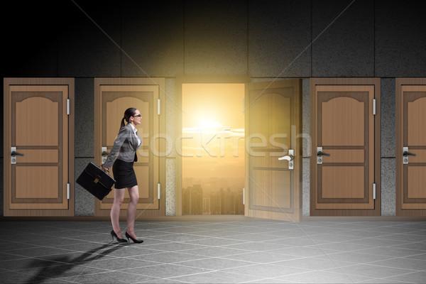 Businesswoman walking towards open door Stock photo © Elnur