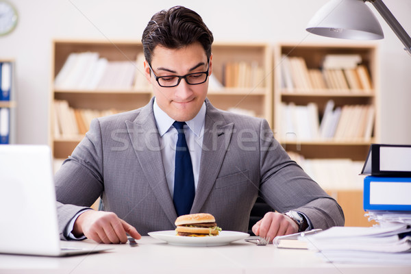 Stock photo: The hungry funny businessman eating junk food sandwich