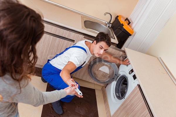 Repairman repairing washing machine at kitchen Stock photo © Elnur