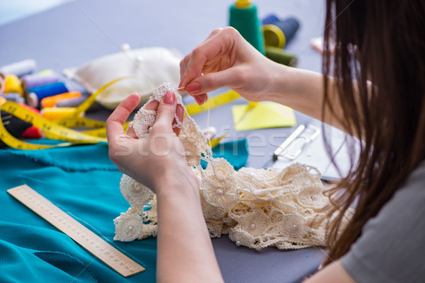 Stock photo: Woman tailor working on a clothing sewing stitching measuring fa