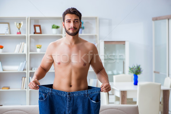 Man in oversized pants in weight loss concept Stock photo © Elnur