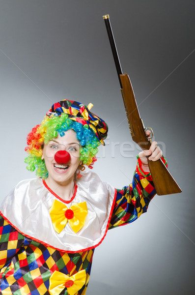 Stock photo: Clown with rifle isolated on white
