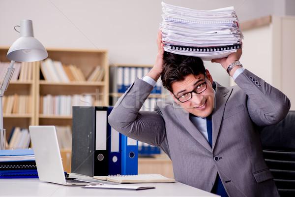 Businessman with too much paperwork Stock photo © Elnur