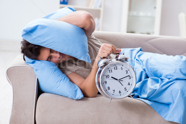 The man having trouble waking up with alarm clock Stock photo © Elnur
