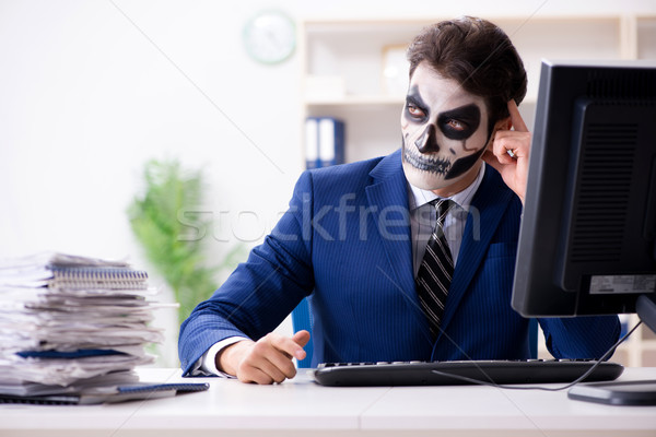 The businessman with scary face mask working in office Stock photo © Elnur