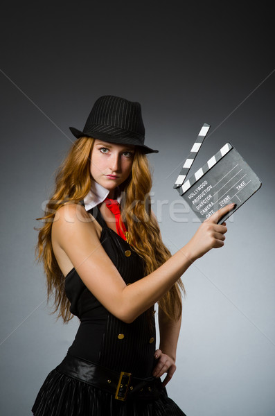 Woman with movie clapboard against grey background Stock photo © Elnur