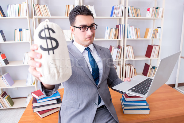 Businessman in library with a money sack and a laptop Stock photo © Elnur