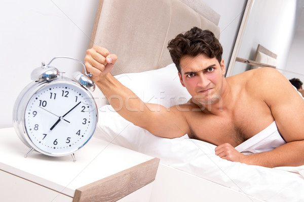 Young man having trouble waking up in the morning Stock photo © Elnur