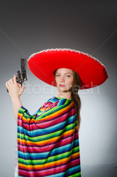 Girl in mexican vivid poncho holding handgun against gray Stock photo © Elnur