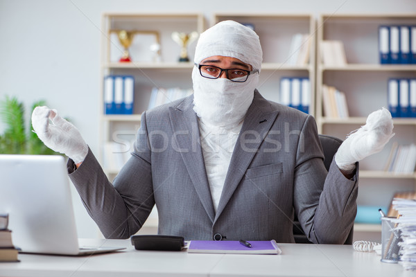 Bandaged businessman worker working in the office doing paperwor Stock photo © Elnur