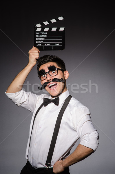 Young man with false moustache holding clapperboard isolated on gray Stock photo © Elnur