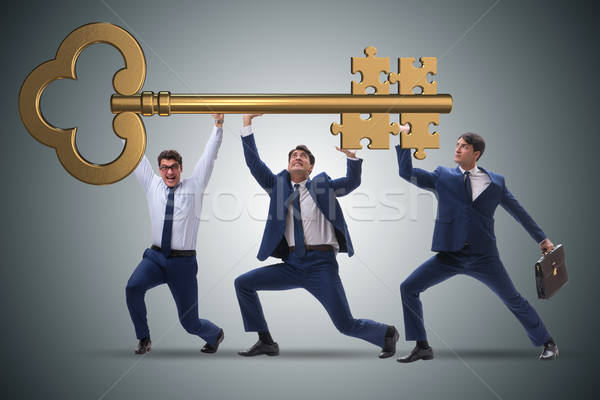 Businessmen holding giant key in business concept Stock photo © Elnur