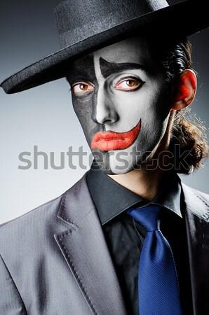 Joker personification with man in dark room Stock photo © Elnur
